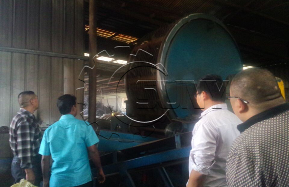 The customer is observing the operation of the tire crusher